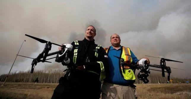 Mat Matthews responsabile di Elevated Robotic Services,e Ron Windmueller, proprietario di Droneology, posano con droni vicino a Fort McMurray, Alberta, Canada,  6 maggio 2016. REUTERS / Chris Wattie