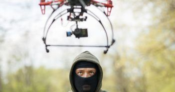57086300 - man in mask operating a drone with remote control. crime concept