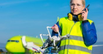 65456530 - airport worker holding crashed quadcopter near airliner